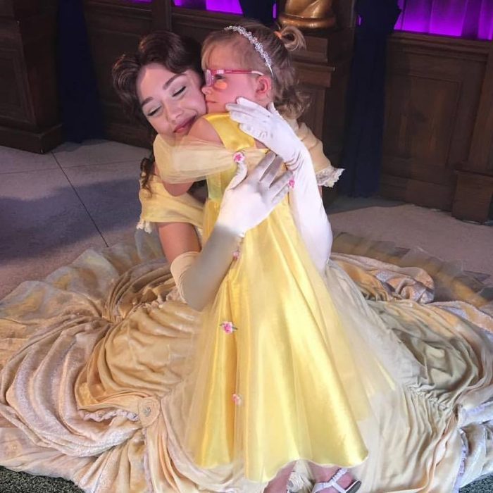 niña disfrazada de bella abraza a Bella en Disney