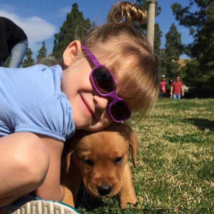 niña con lentes abrazando a un perro