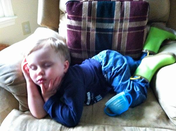 Niño durmiendo en un sofá como si estuviera posando