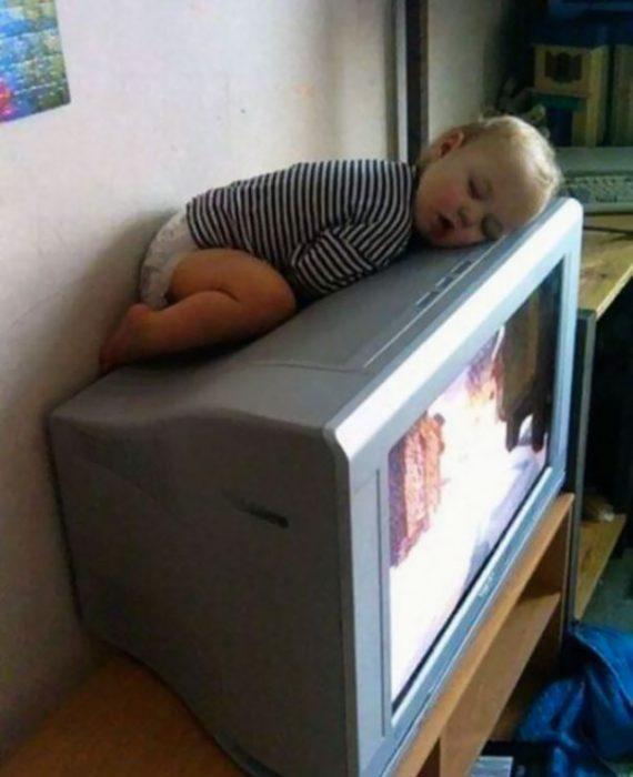 Niño durmiendo sobre la parte de arriba de una televisión