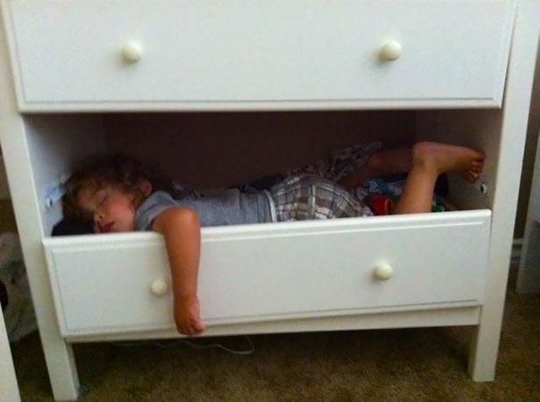 Niño durmiendo dentro de los cajones de una cómoda
