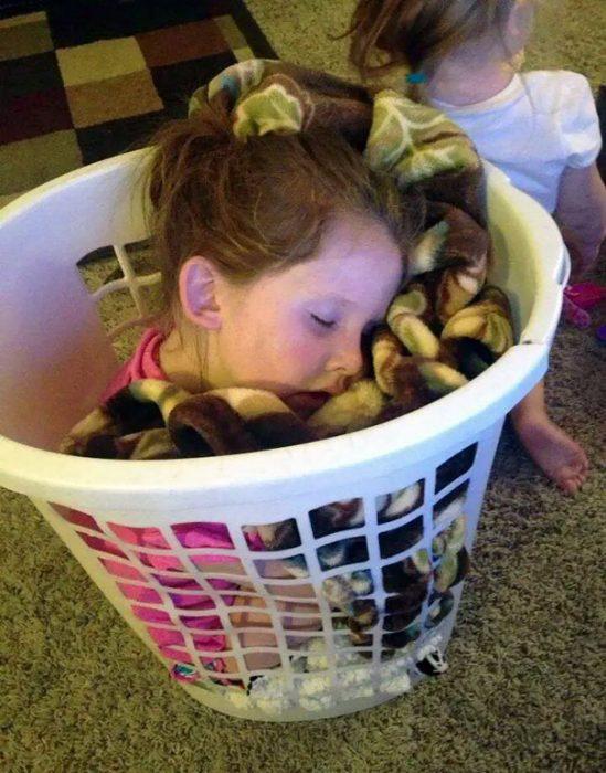 Niña durmiendo dentro de un cesto de ropa