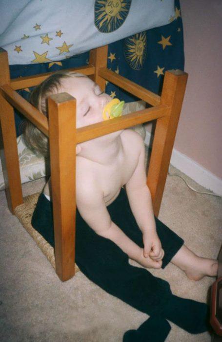 Niño durmiendo sobre una silla volteada