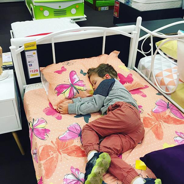 Niño durmiendo sobre una cama de exhibición en una tienda