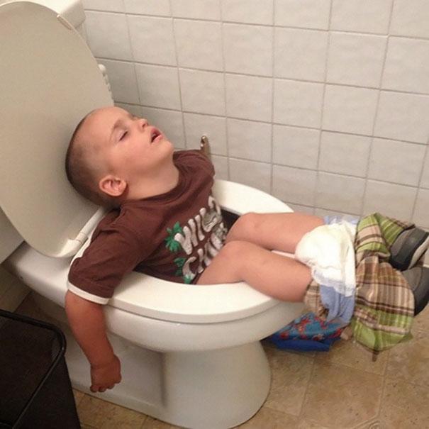 Niño durmiendo mientras está sentado en el baño