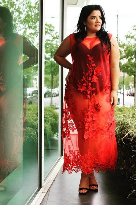 Chica curvi usando un vestido rojo con transparencias
