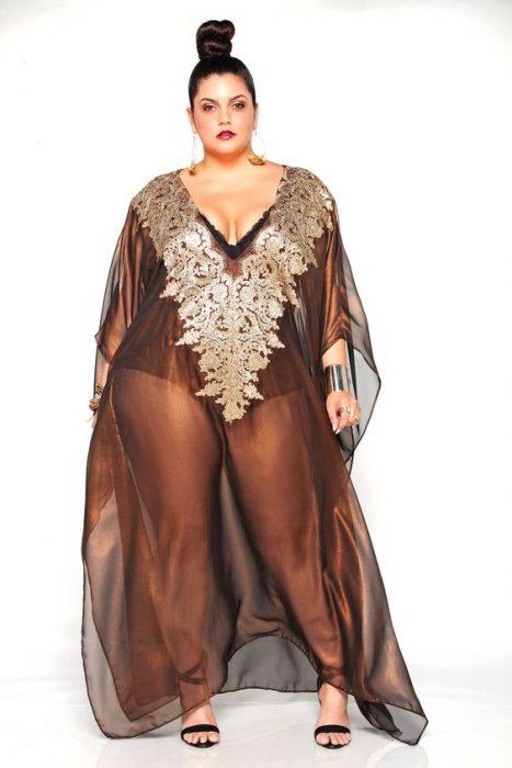 Chica curvi usando un vestido color cobre con transparencias