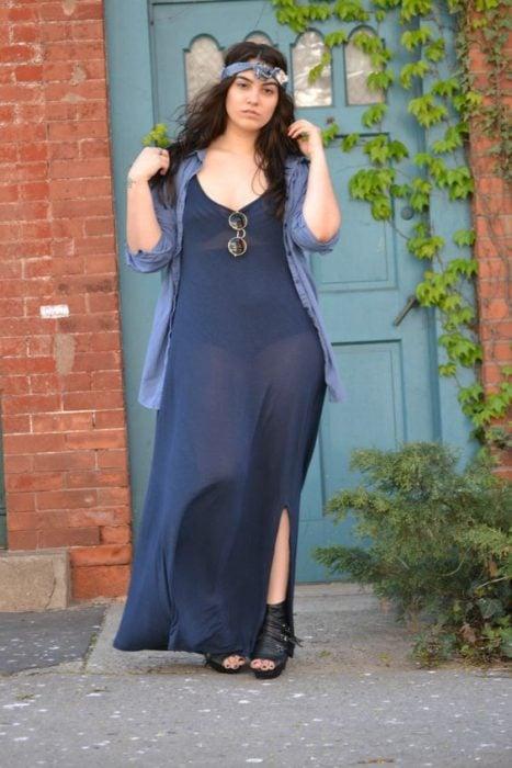 Chica curvi usando un vestido largo con transparencias