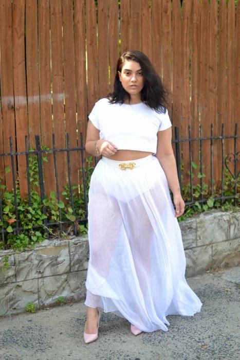 Chica curvi usando una falda blanca con transparencias