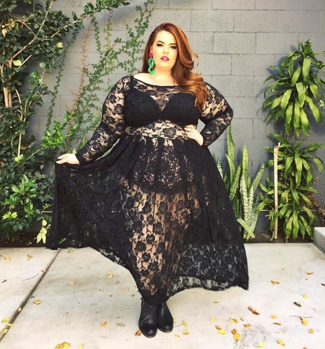 Chica curvi usando un vestido negro de encaje con transparencias