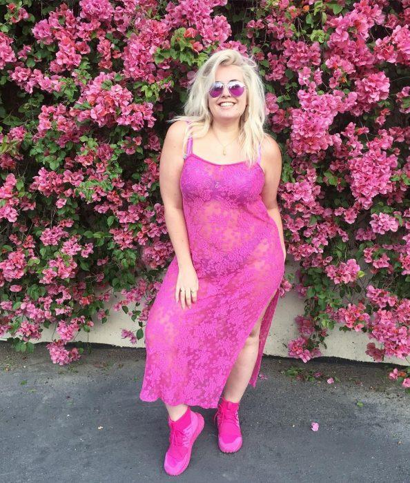 Chica curvi usando un vestido rosa con transparencias