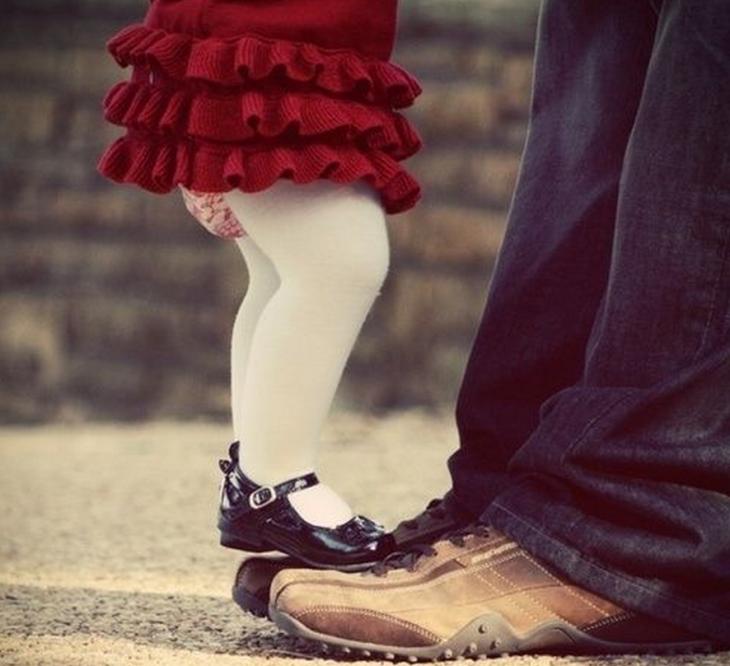 hombre con zapatos cafe y niña con zapatos de charol sobre pies de hombre