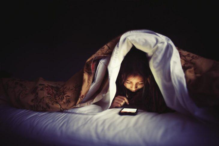 chica viendo celular en la oscuridad