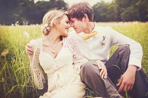 Pareja de novios sentados sobre el pasto mirándose