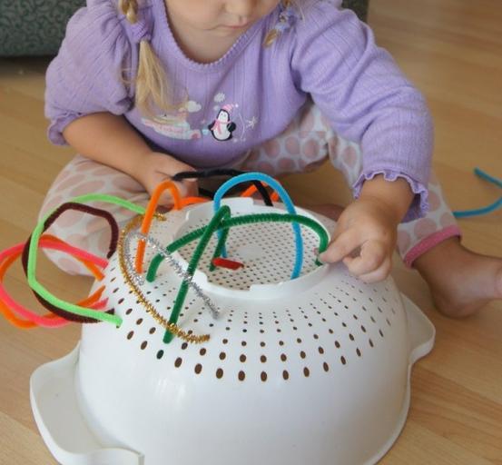 Niña jugando con una colador de cocina.
