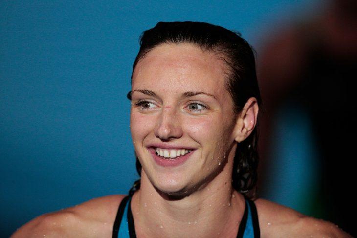 mujer rubia mojada con traje de baño sonriendo