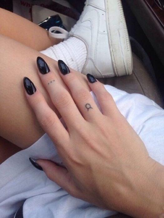 Chica con un tatuaje del signo tauro en un dedo