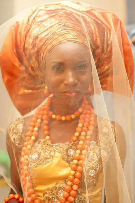 Novia de Nigeria usando un vestido en color naranja