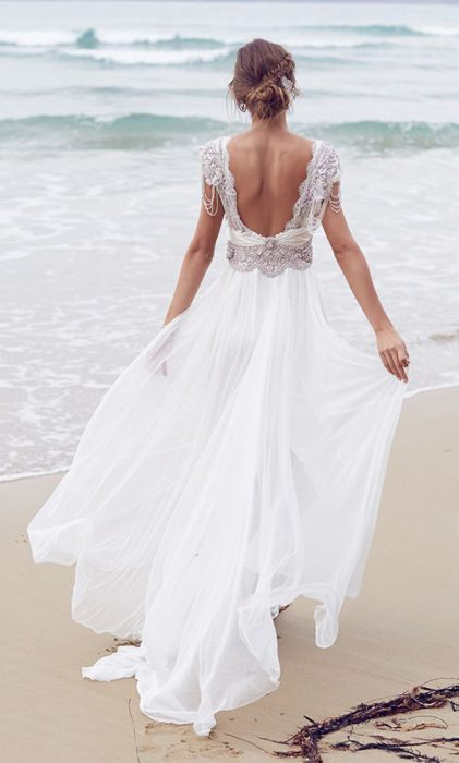 Girl in a wedding dress with backless walking on the beach