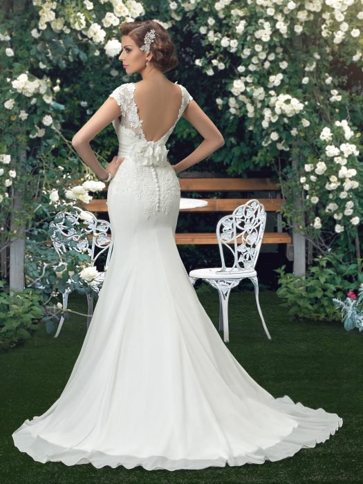 Girl in a wedding dress with backless posing for a photo shoot
