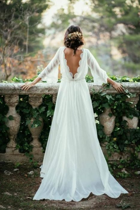 Girl in a wedding dress with neckline stop back on a stone railing