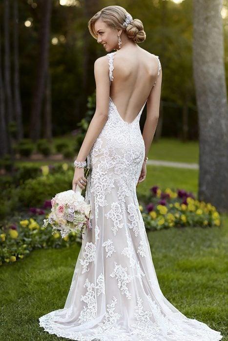 Chica con un vestido de novia con escote en la espalda parada afuera en un jardín
