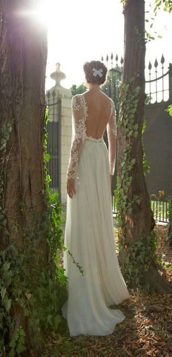 Girl in a wedding dress with backless between two trees