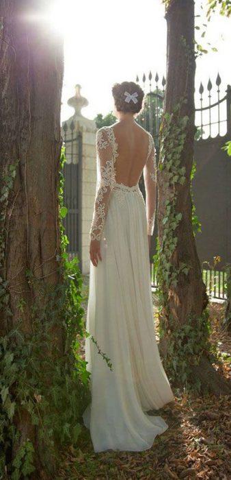 Chica con un vestido de novia con escote en la espalda entre dos árboles