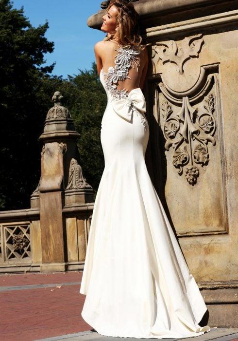 Chica con un vestido de novia con escote en la espalda parada sobre una columna de cantera