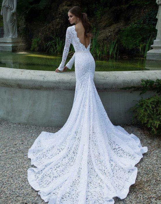 Chica con un vestido de novia con escote en la espalda parada frente a una fuente