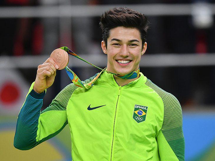hombre con madalla y chamarra verde sonriendo