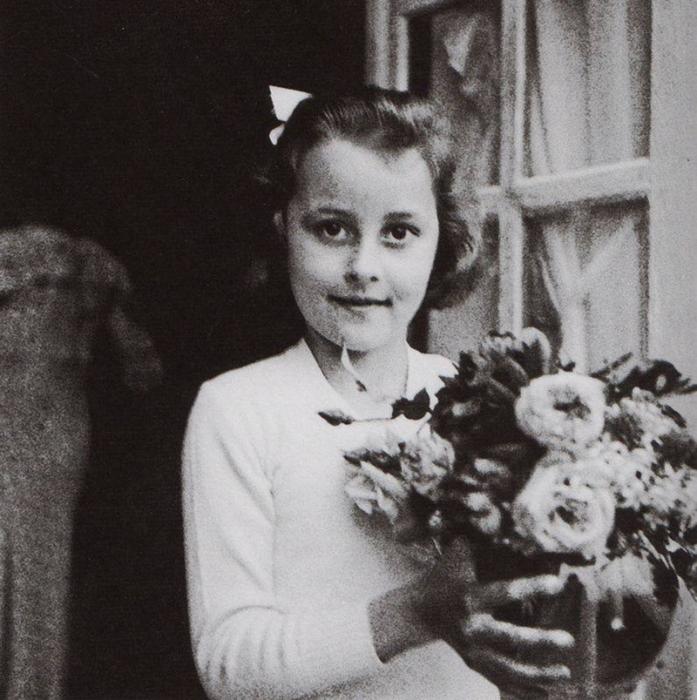 niña con moño y flores en la mano