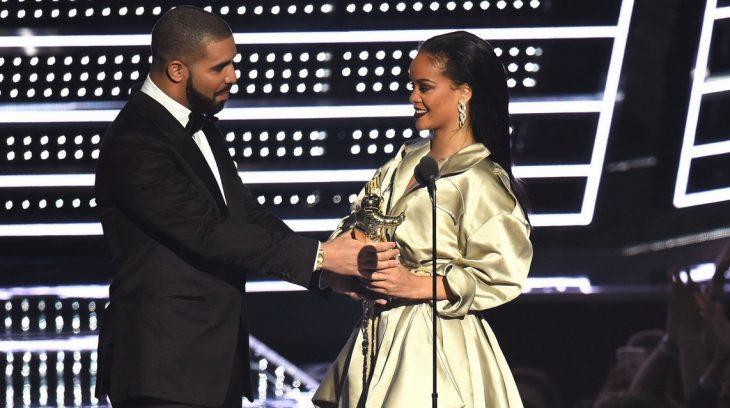 hombre le entrega premio a mujer en escenario vmas