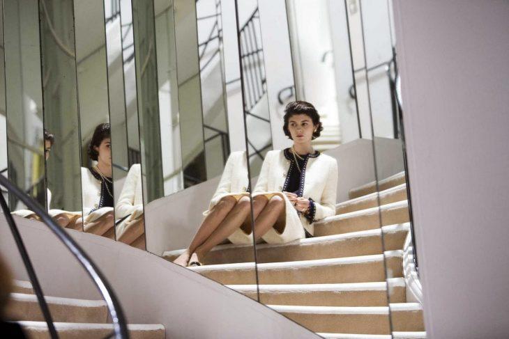 mujer con traje blanco sentada en escaleras con espejos