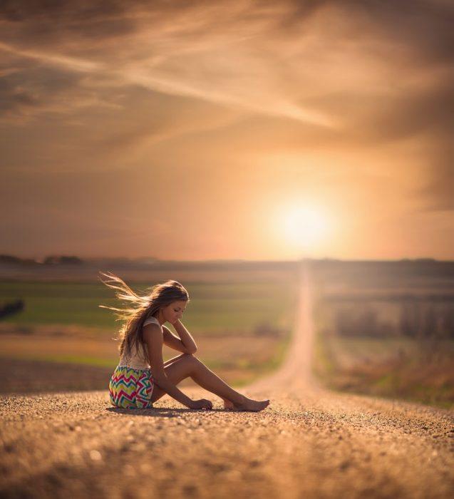 Chica sentada a mitad de la carretera
