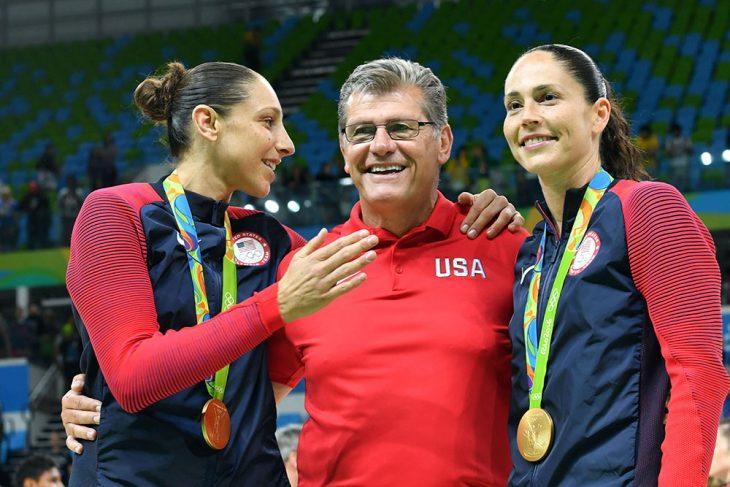 hombre entrenador al lado de dos mujeres con medalla de oro