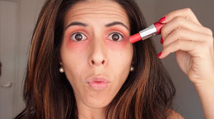 Aplicando labial color naranja.