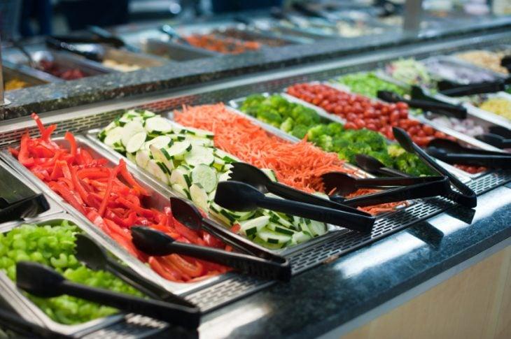 barra de ensaladas con pinzas negras