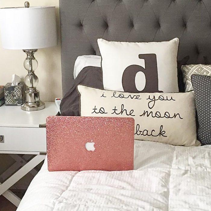 lap top rosa mac en cama con almohadas