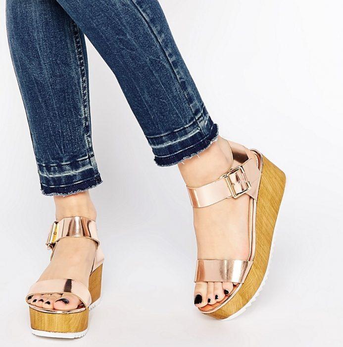 piernas de mujer con sandalias de color rose gold y plataforma