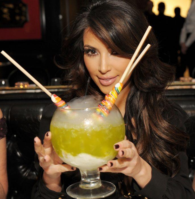 mujer morena con una bebida grande y paletas