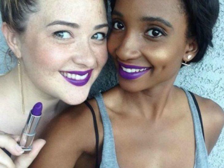 Dos mujeres de piel blanca y morena con labial purpura