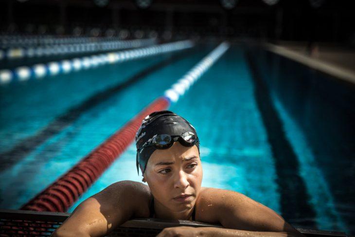 mujer con gorra y googles recargada en orilla de piscina