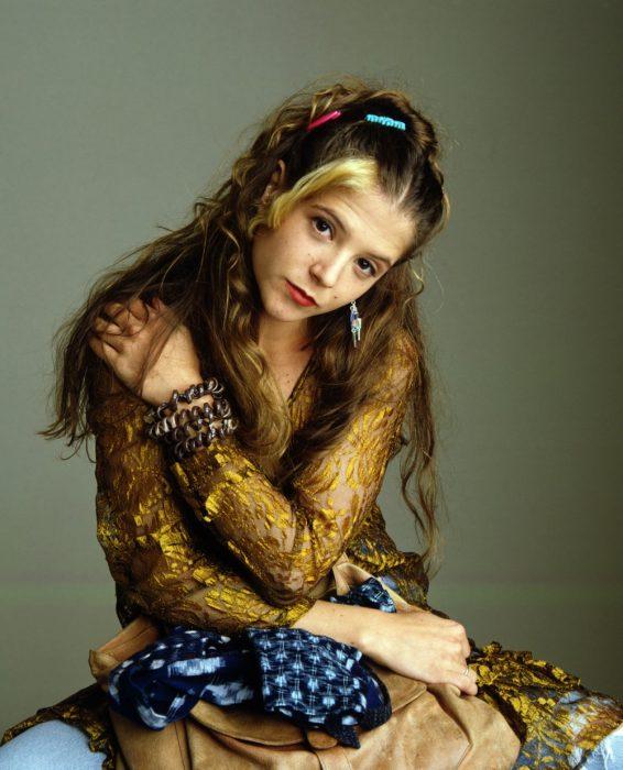 mujer con brazos cruzados y cabello castaño con mechon rubio