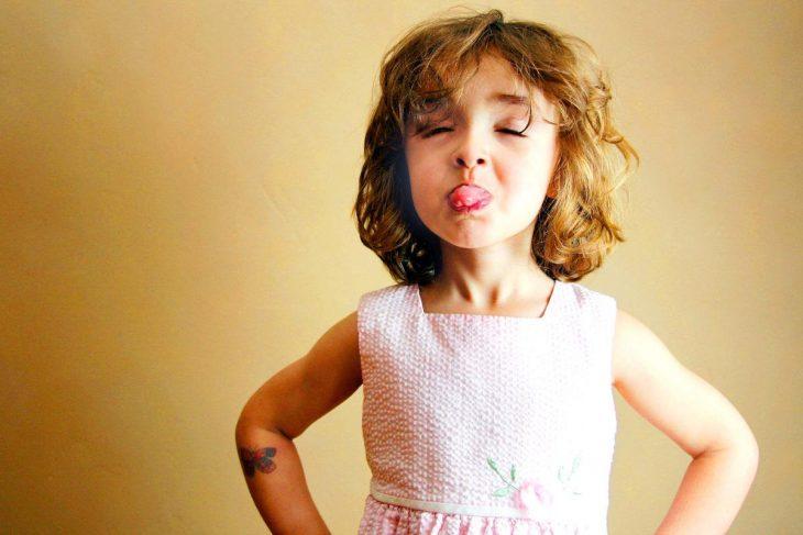 niña de cabello corto sacando la lengua con brazos en la cintura