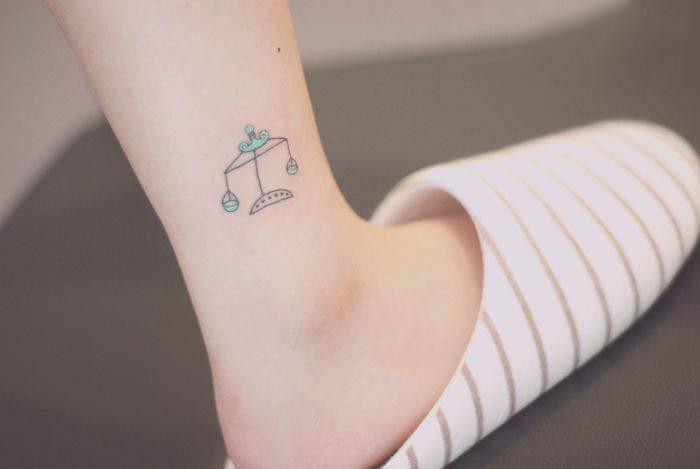Chica con un tatuaje de una balanza en su pie