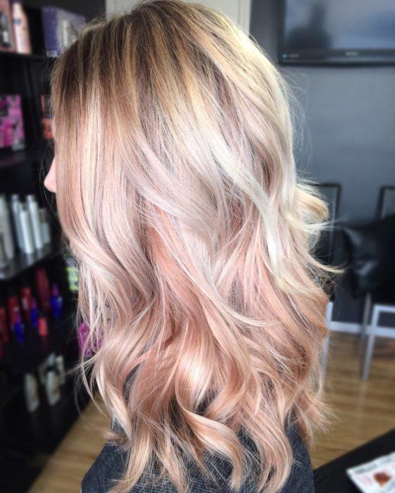 Chica de perfil con el cabello rosa dorado.