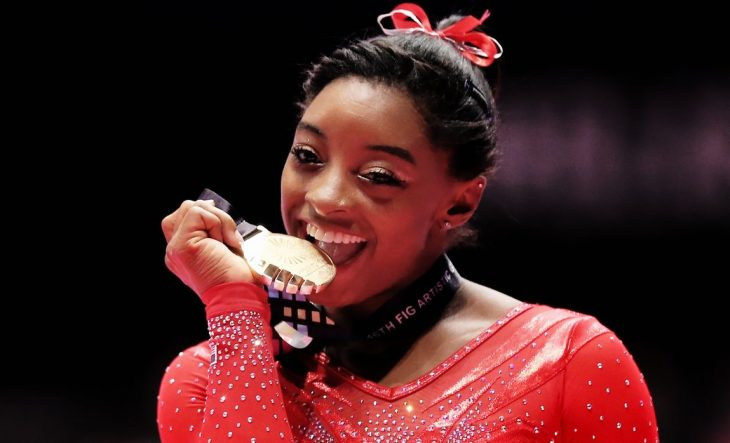 mujer con traje rojo besando su medalla