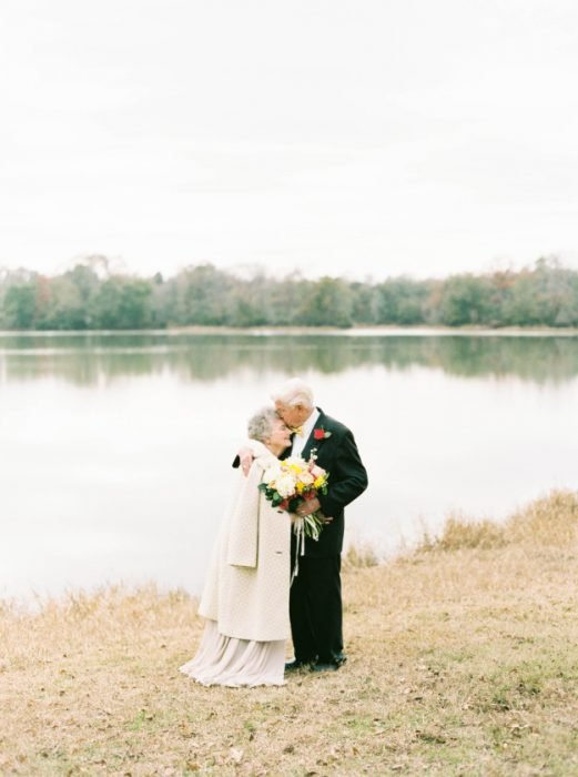 Abuelos besándose a la orilla de un lago.