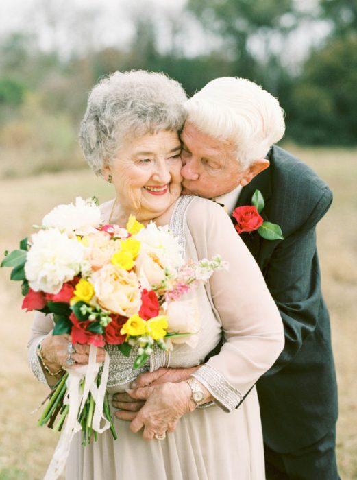 Abuelo besando a la novia en el cachete.